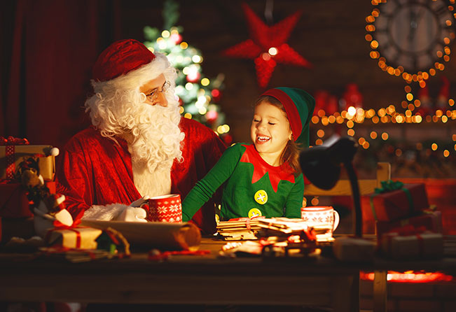 Santa sitting laughing with child elf