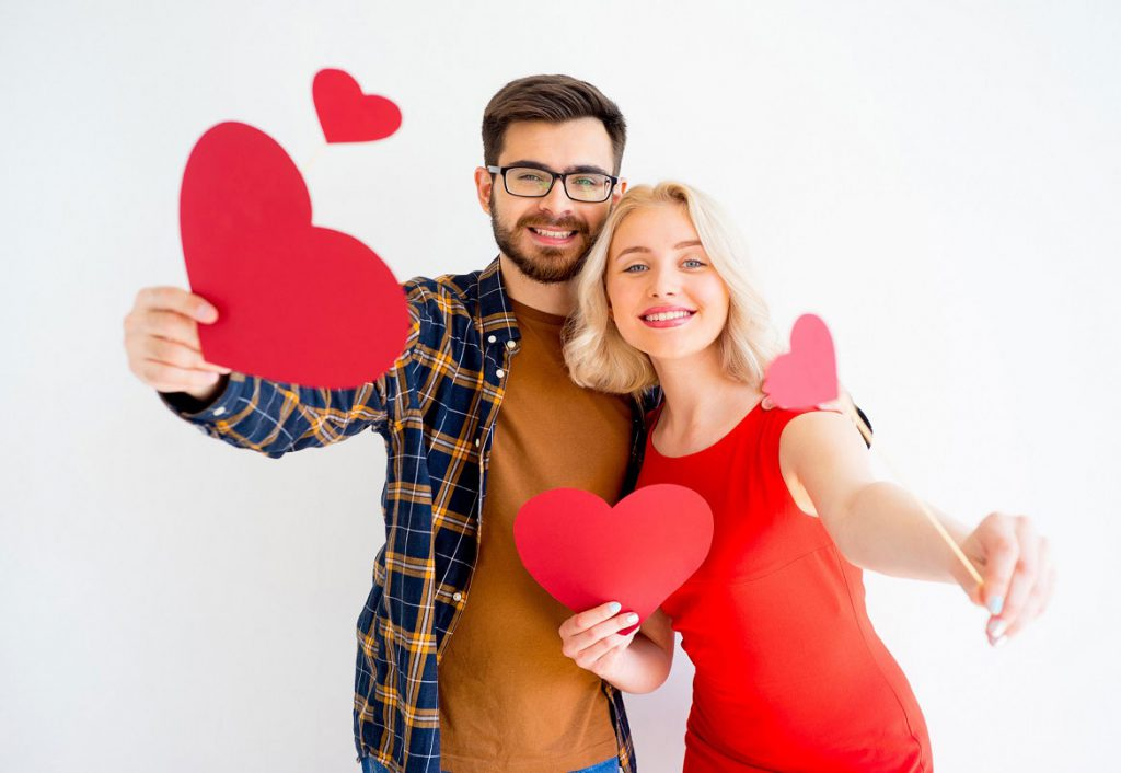 Couple holding paper hearts and smiling