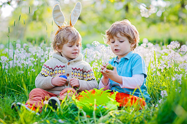 children sitting on grass with easter eggs