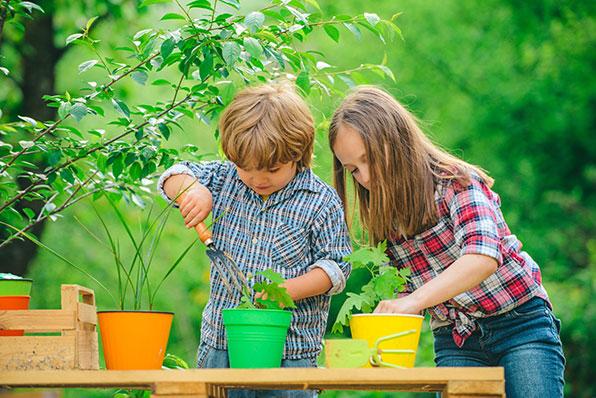 children planting flowers in pots