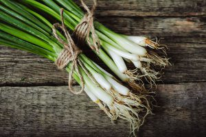 spring onions on wooden board