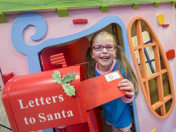 Girl posting letter to Santa